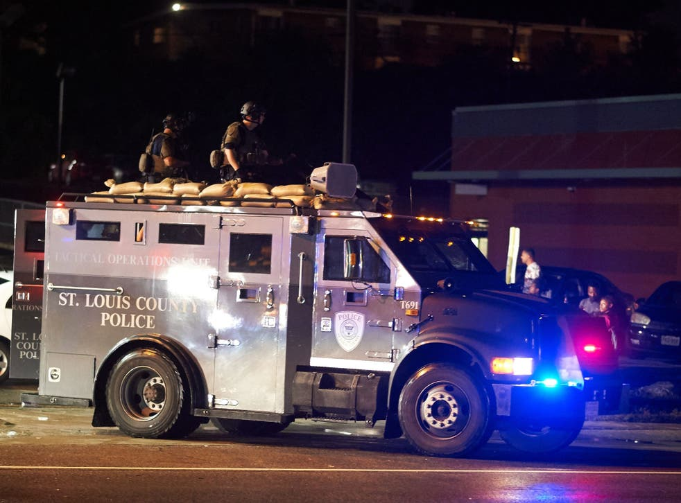 St. Louis County  police officers respond in an MRAD vehicle after shots were fired during a protest march on August 9, 2015 on West Florissant Avenue in Ferguson, Missouri