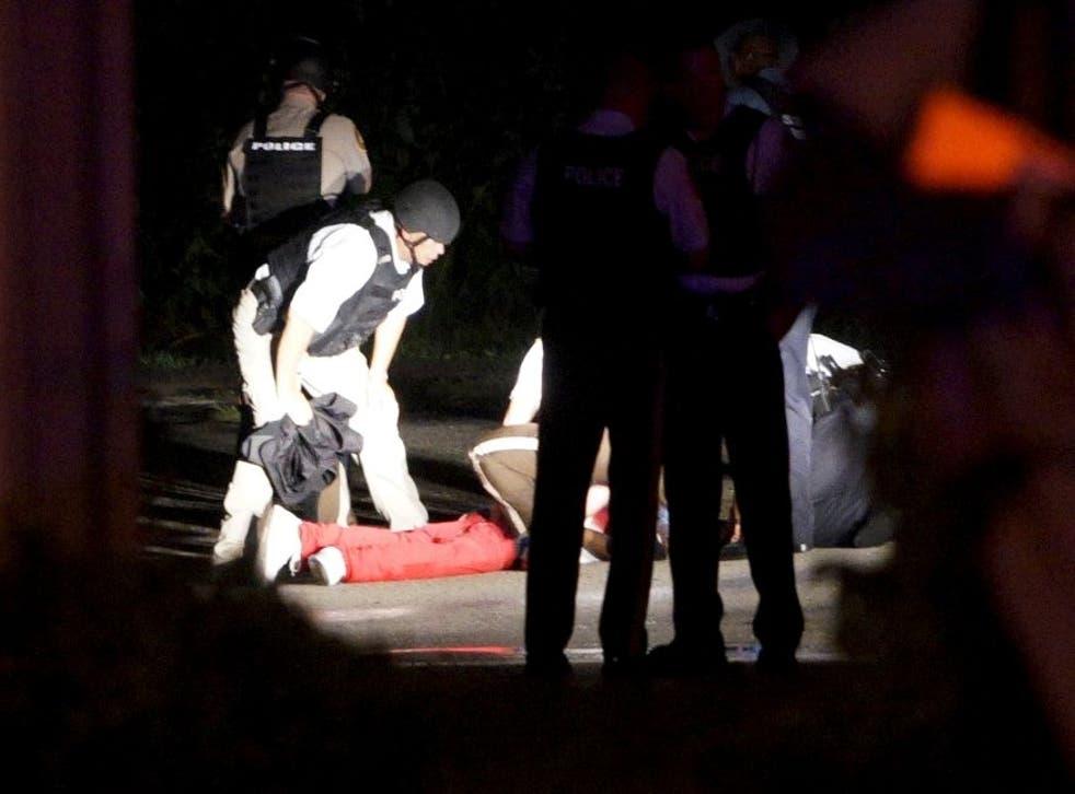 The man named as Tyrone Harris lies on the floor