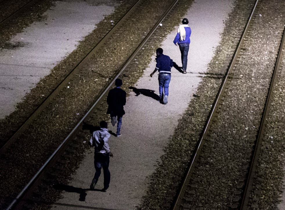 Migrants run on the shuttle tracks after they succeeded to jump over the fences and avoid the French patrols on the outskirts of Calais.