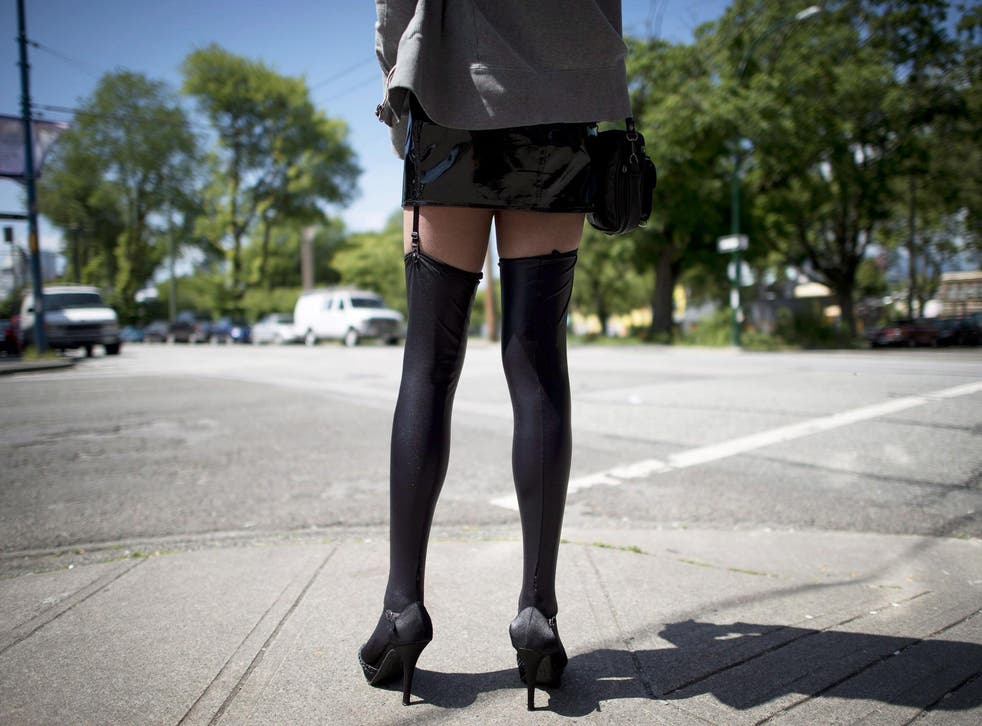 A sex trade worker stands on a corner in downtown Vancouver