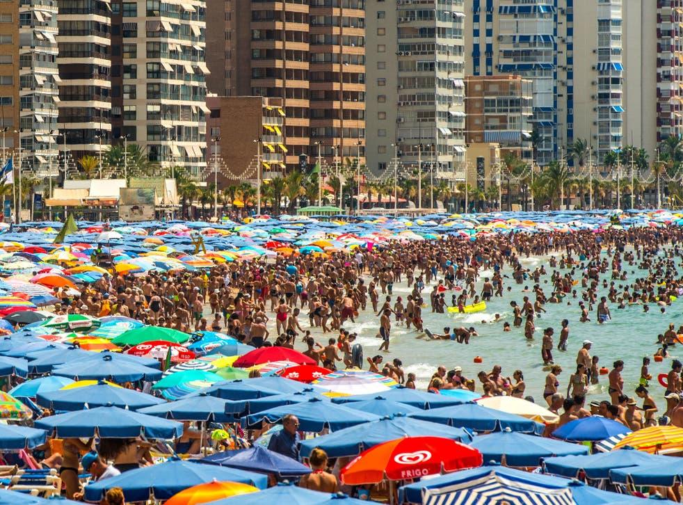 Crowds sunbathe at Levante beach in Benidorm, Spain