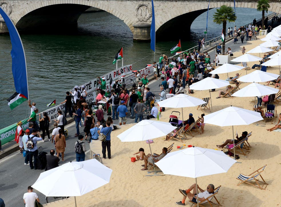 Palestinian supporters hold placards in front of people sunbathing at Tel Aviv sur Seine in Paris