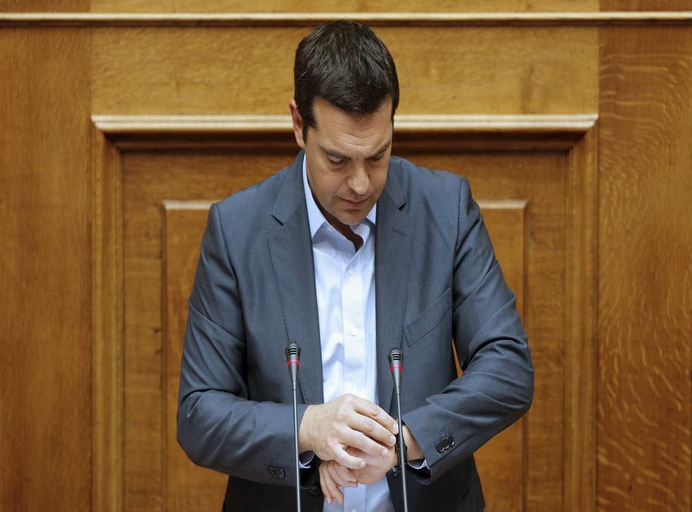 Greek Prime Minister Alexis Tsipras checks his watch as he delivers his speech at the end of a night parliamentary session in Athens, Greece, August 14, 2015 (REUTERS/Christian Hartmann)