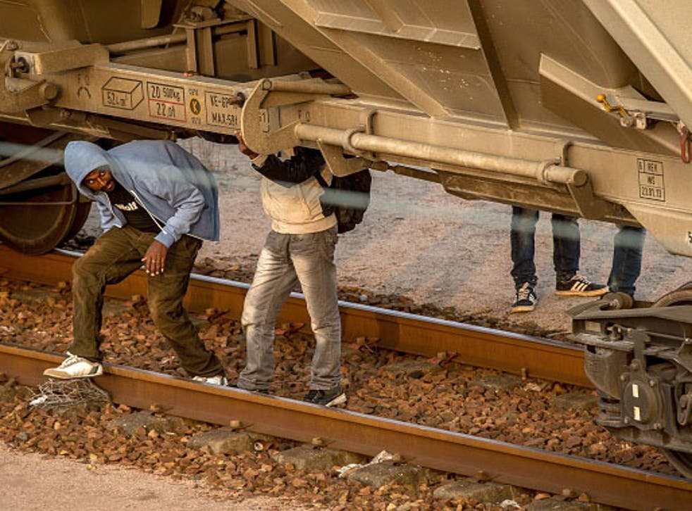 Migrants hide under a freight car in Coquelles near Calais pm on their way to the Eurotunnel on 12th August