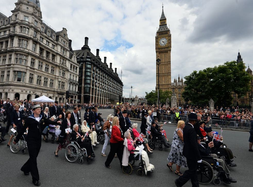 Veterans and serving members of the British Armed Forces march past Big Ben on VJ Day