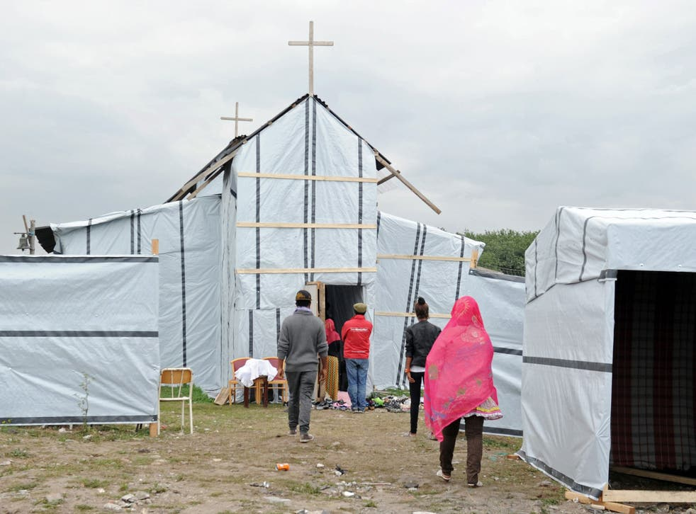 Migrants enter into the makeshift church built in the migrant camp called the 'new jungle' in Calais, near The Jungle.