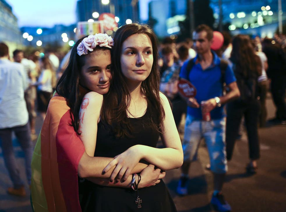 Two women hug in front of the Greek Parliament in Athens during a Gay Pride parade