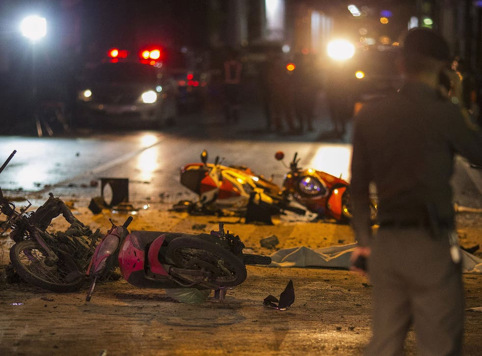 Debris and overturned motorcycles are strewn across the intersection across from the Erawan Shrine after an explosion in Bangkok