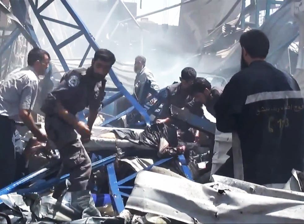 Rescuers carry a victim from the site of Syrian government airstrikes in Douma, a suburb of Damascus