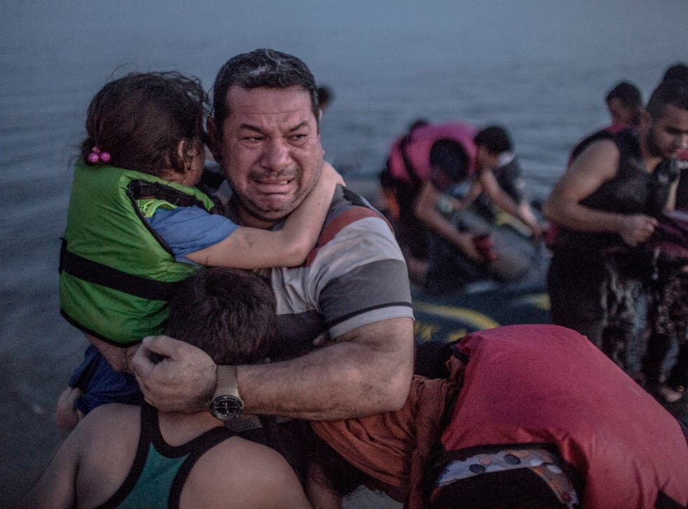 A Syrian father holds his children close as his arrives on the Greek Island of Kos
