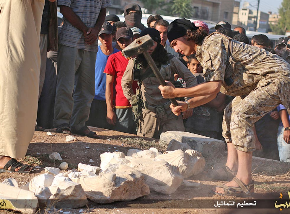 An image posted on an Isis affiliated website shows a militant smashing items from Palmyra