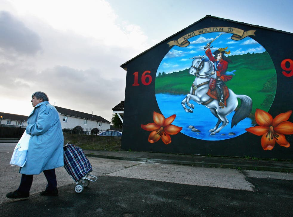 A woman walks past a protestant loyalist mural in the Shankhill area