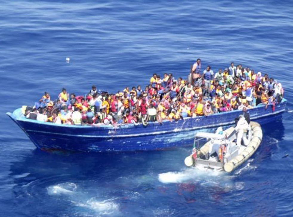 An Italian navy dinghy approaches a crowded migrant boat in the Mediterranean