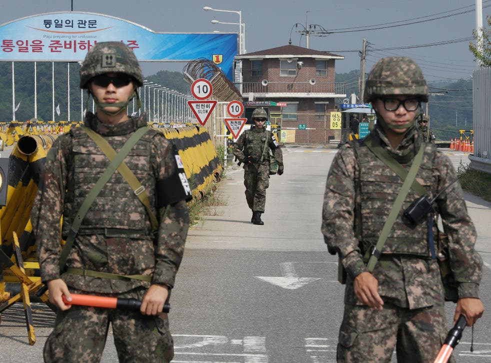 A South Korean amy soldier walks as his colleague soldiers stand guard on Unification Bridge, which leads to the demilitarized zone (AP)