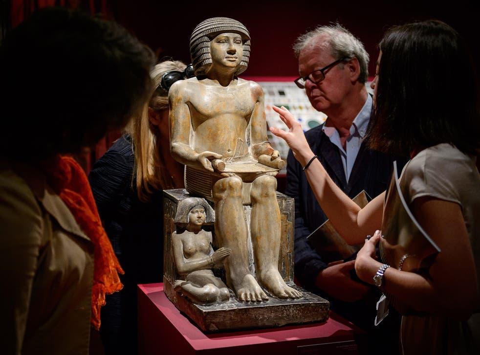Members of the public and gallery staff examine The Northampton Sekhemka, an Egyptian painted limestone statue