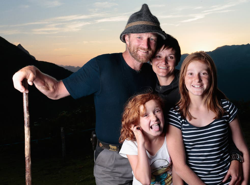 Alpine cattle herder Martin Riedmann (L), his wife Veronica (2R) and their daughters Selina (R) and Sabrina pose for a picture in front of alpine dairy Alpe Albona in the Vorarlberg mountain range of western Tyrol