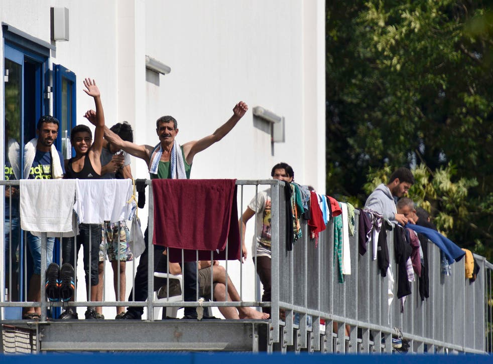 Migrants wave as they stand on the staircase of an asylum seekers accomodation facility in the eastern German town of Heidenau (Reuters)