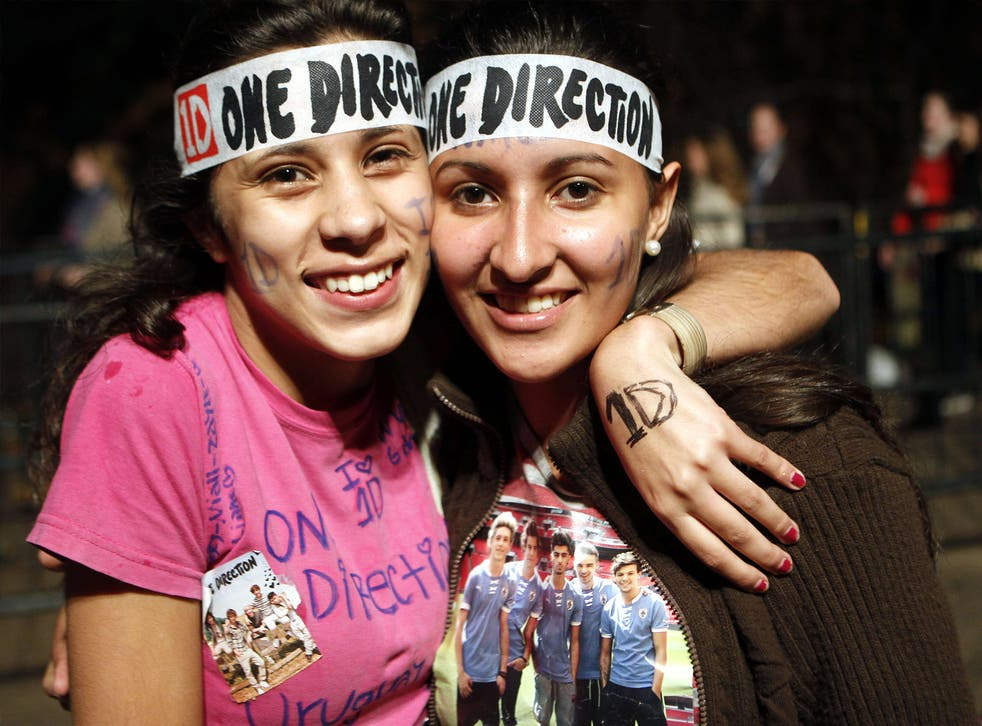 Two Directioners pose for a photo at a One Direction concert in Uruguay, 2014