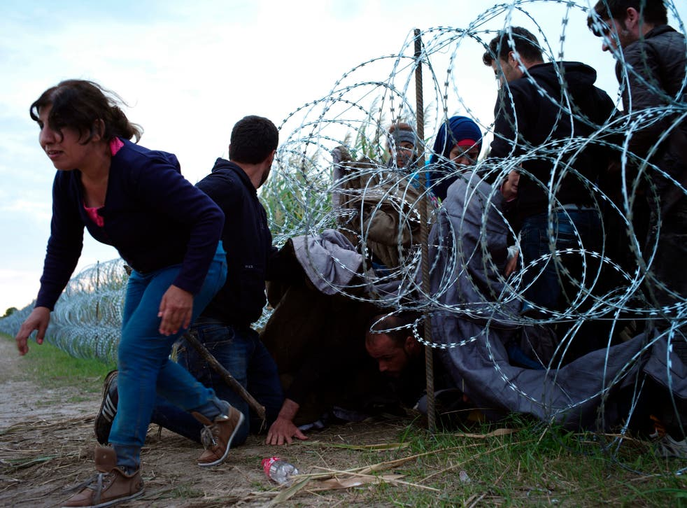 Syrian refugees cross into Hungary underneath the border fence on the Hungarian/Serbian border near Roszke, Hungary