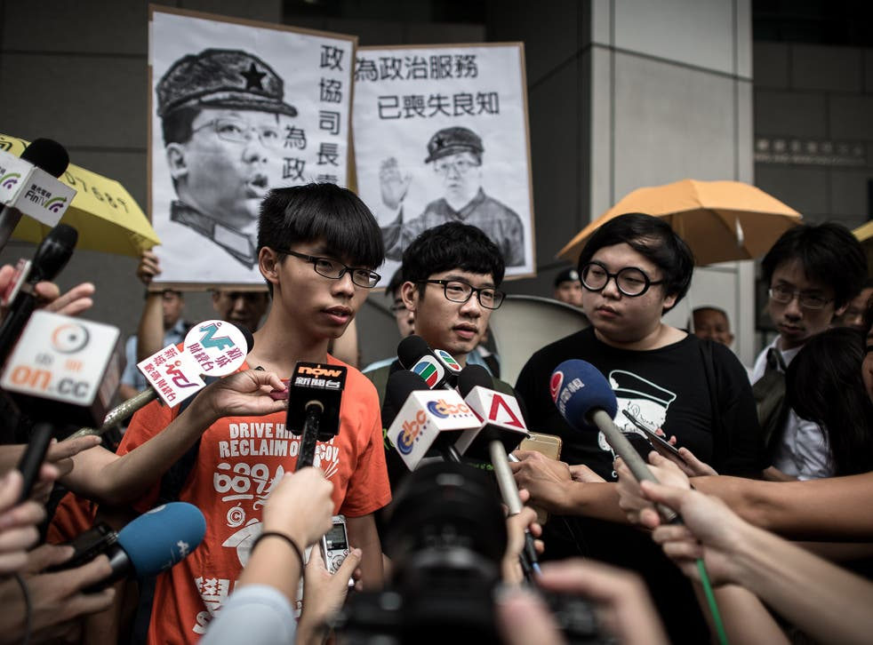 Student protesters Joshua Wong (L) and Nathan Law (C) talk to the media outside the Wanchai police station in Hong Kong on August 27, 2015