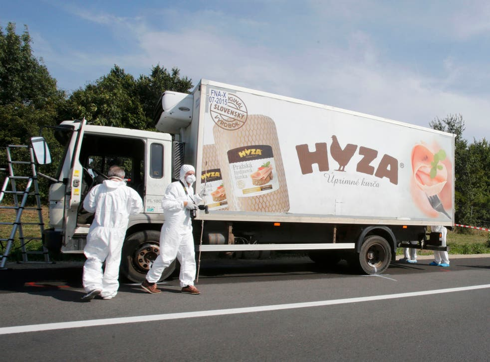Forensic police officers inspect a parked truck in which up to 50 migrants were found dead, on a motorway near Parndorf, Austria