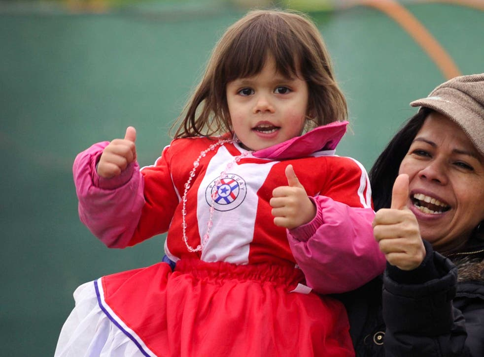 A young girl smiles as she wears Paraguay's flag as a dress