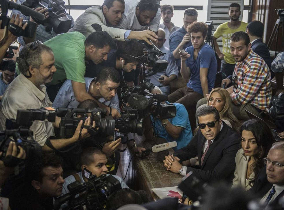International media forms a scrum around Mohammad Fahmy, wife Mawra and their lawyer Amal Clooney in the court