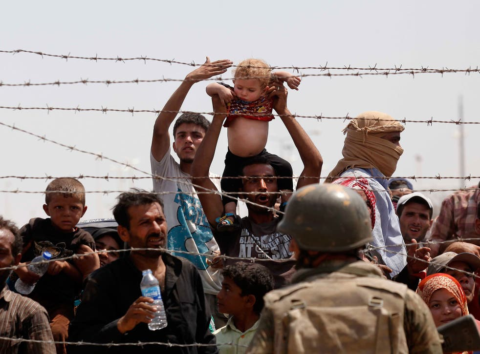 Syrian refugees passing on the Syrian side of the border crossing Akcakale, in Sanliurfa province, southeastern Turkey