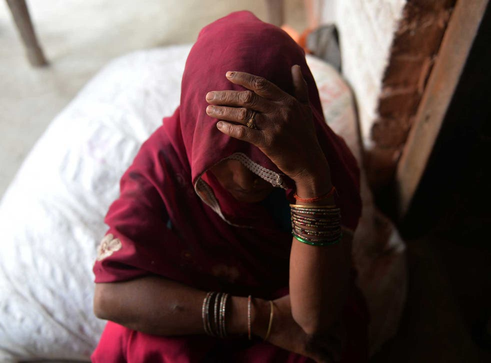 An Indian woman hides her face: in Baghpat villager, locals deny the sisters' tale