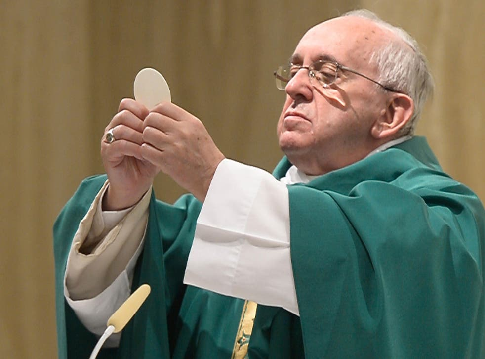 This handout picture released by the Vatican press office (Osservatore Romano) shows Pope Francis holding up sacramental bread as he celebrates mass in Santa Marta at the Vatican on September 1, 2015