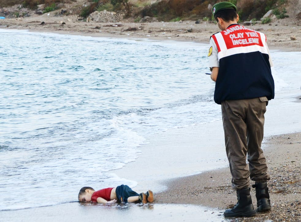 A young Syrian boy, who drowned in his family's attempt to reach Greece from Turkey, lies in the surf near Bodrum, Turkey