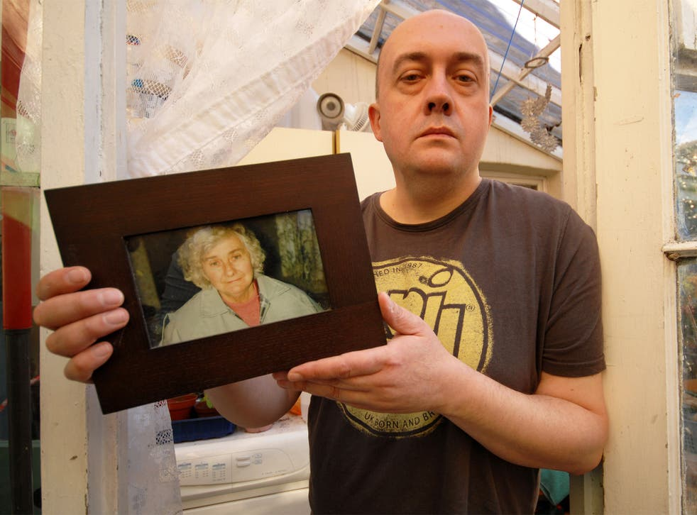 Simon Cooke with a picture of his mother, Barbara, who died days after being admitted to hospital from her care home