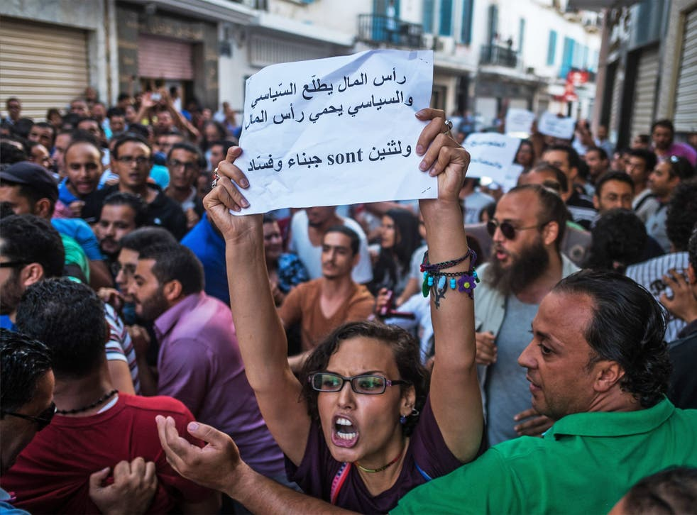 Demonstrators rally in Tunis on Tuesday against a planned financial amnesty for members of former President Zine el-Abidine Ben Ali's regime. Some protesters were beaten up and arrested