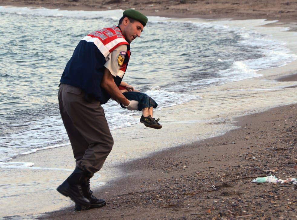 A paramilitary police officer carries the body of Aylan Kurdi, who drowned last September