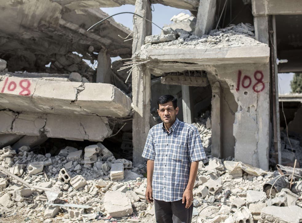 Abdullah Kurdi stands in front of his neighbour's house in Kobane