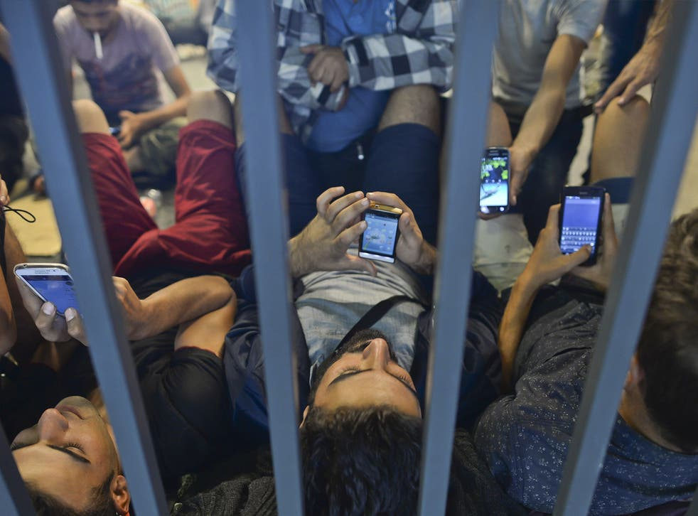Refugees at Budapest Railway station check their phones