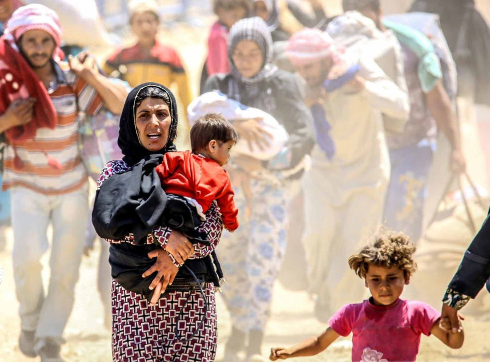 Syrians fleeing the clashes in the city of Tal Abyad and crossing into Turkey earlier this year
