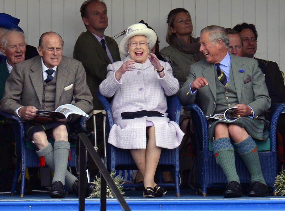 Members of Britain's royal family (front L to R) Prince Philip, Queen Elizabeth and Prince Charles cheer as competitors participate in a sack race at the Braemar Gathering in Braemar, Scotland, 2012