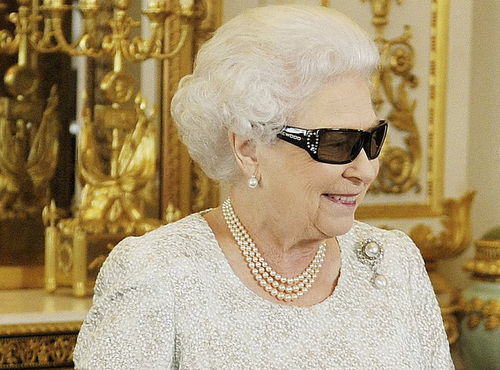 """Queen Elizabeth watches a preview of her Christmas message wearing a pair of 3D glasses, studded with Swarovski crystals in the form of a """"Q"""", at Buckingham Palace in central London, 2012"""