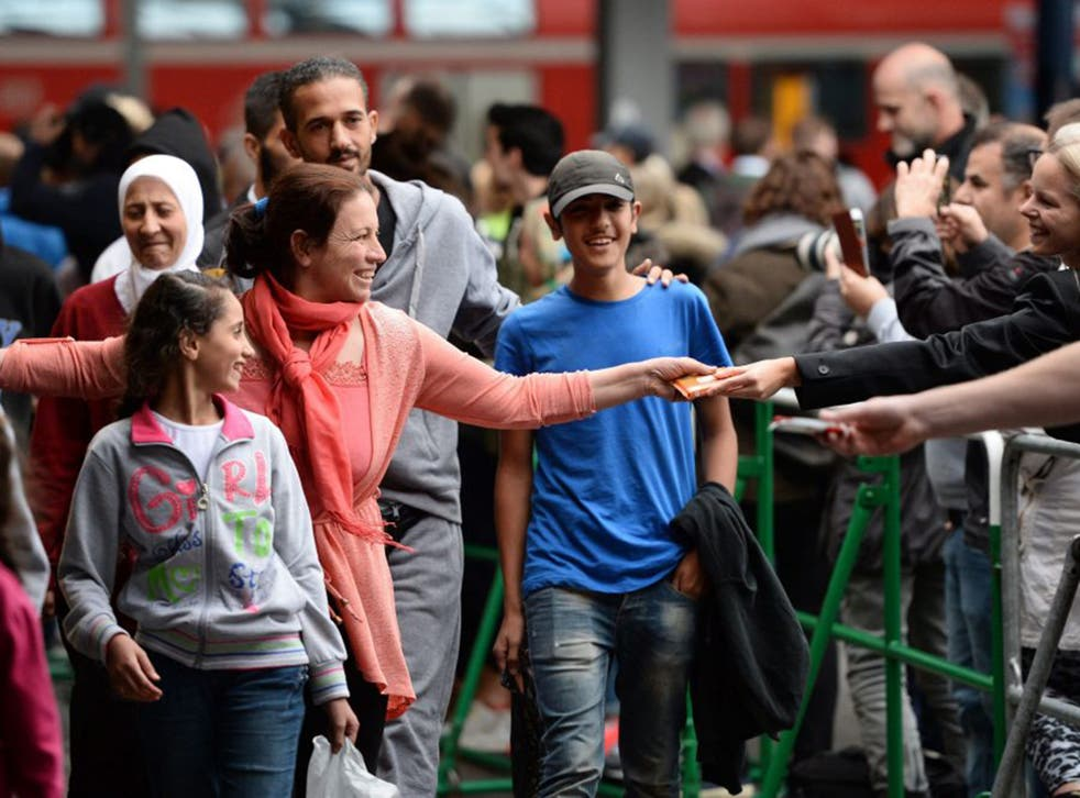 Refugees arrive at the central railway station in Munich, welcomed with open arms