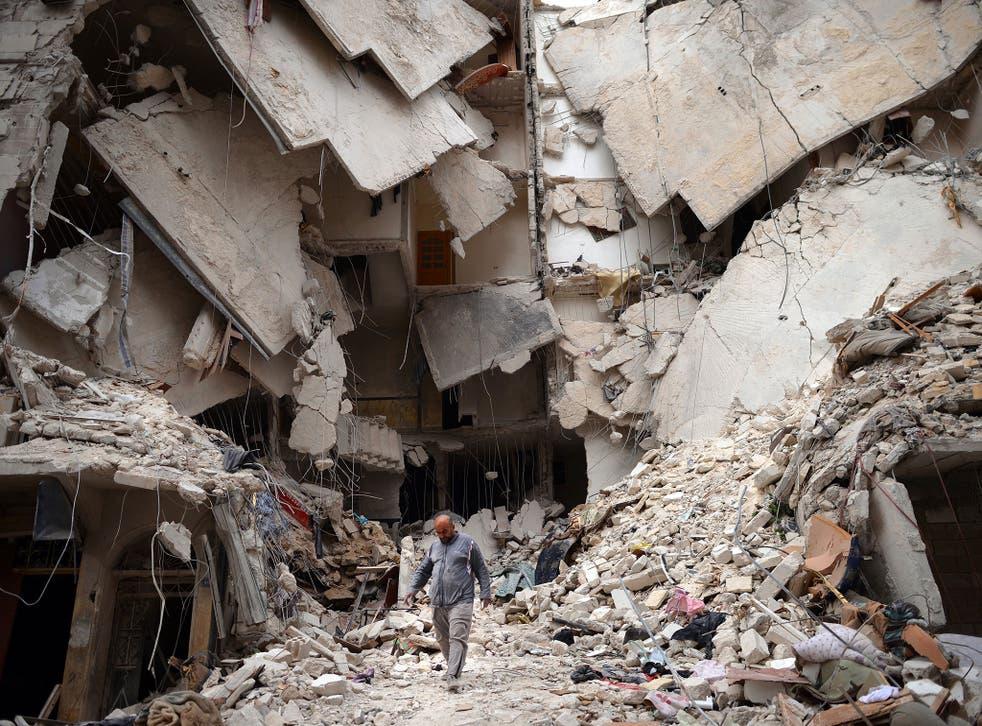A Syrian man walks amid destruction in the northern Syrian city of Aleppo