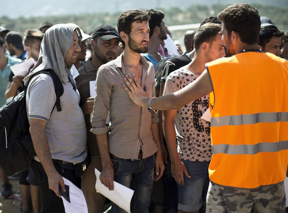 Refugees, mainly from Syria, wait at a registration center held at a stadium on the Greek island of Lesbos