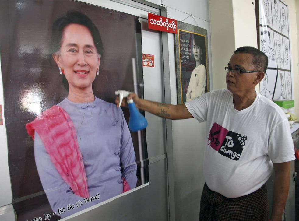 A supporter cleans a portrait of Aung San Suu Kyi at the NLD's headquarters in Yangon