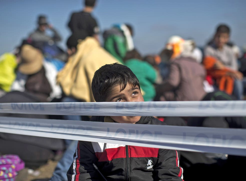 A child sits at a temporary holding camp for refugees close to the Serbian border in Roszke, Hungary
