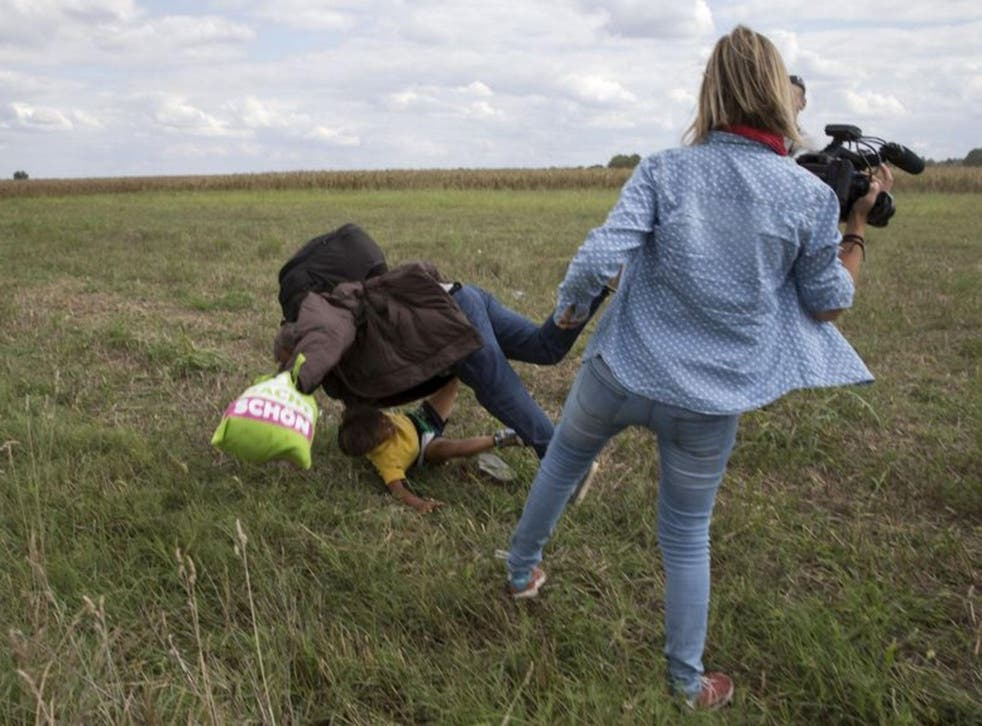 A refugee carrying a child falls after tripping on a TV camerawoman while trying to escape from a collection point in Roszke village