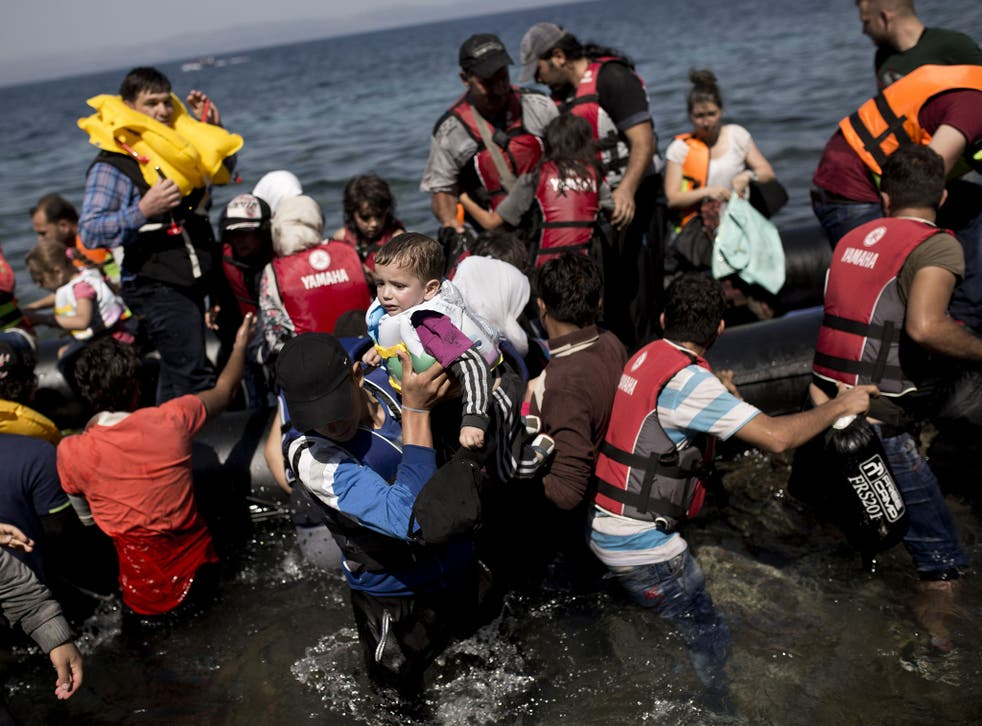 Syrian refugees arrive on the shores of the Greek island of Lesbos after crossing the Aegean Sea from Turkey on a inflatable dinghy on September 11, 2015