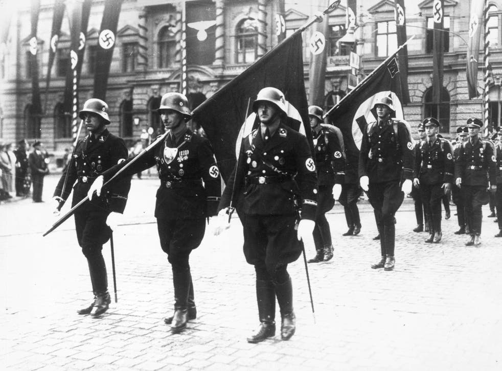 Nazi stormtroopers in Weimar, carrying swastika flags in ceremonial dress