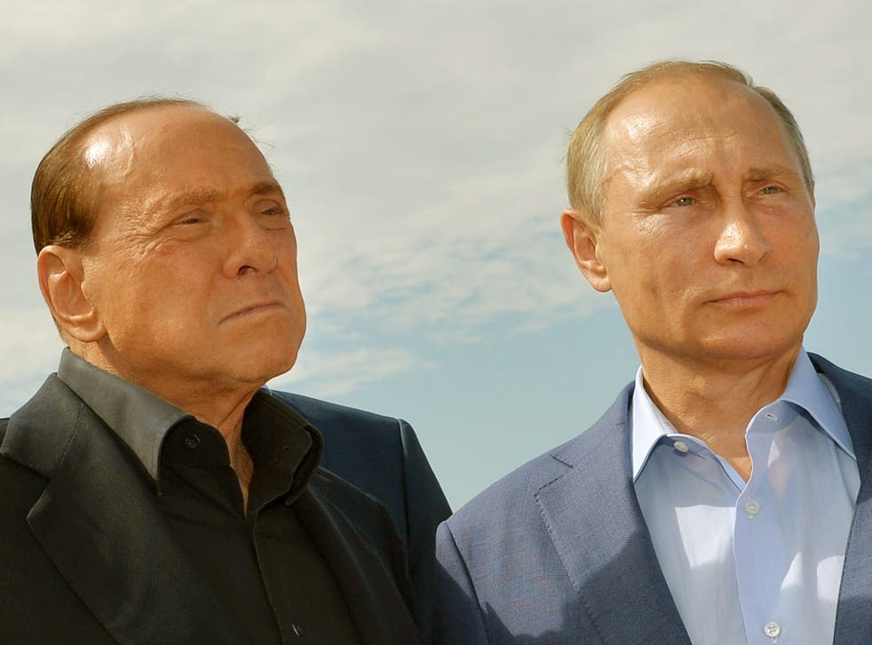 Russian President Vladimir Putin (R) and former Italy's prime minister Silvio Berlusconi visit an Italian war cemetery near the Black Sea port of Sevastopol