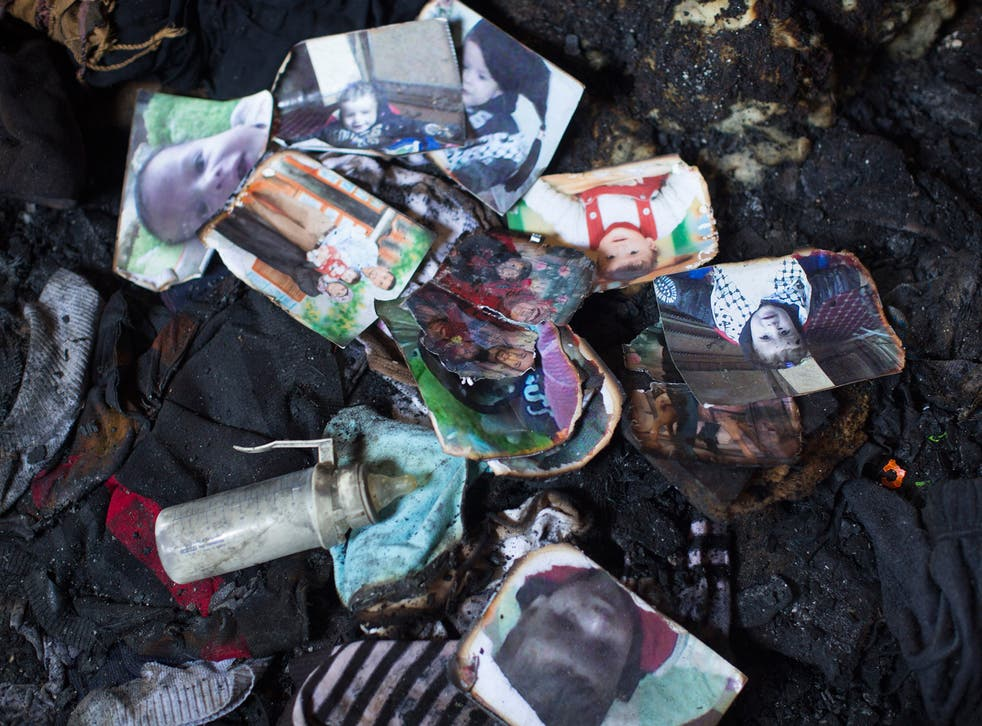 Photos of the Dawabsheh family lie in a burnt pile among the ruins of their house
