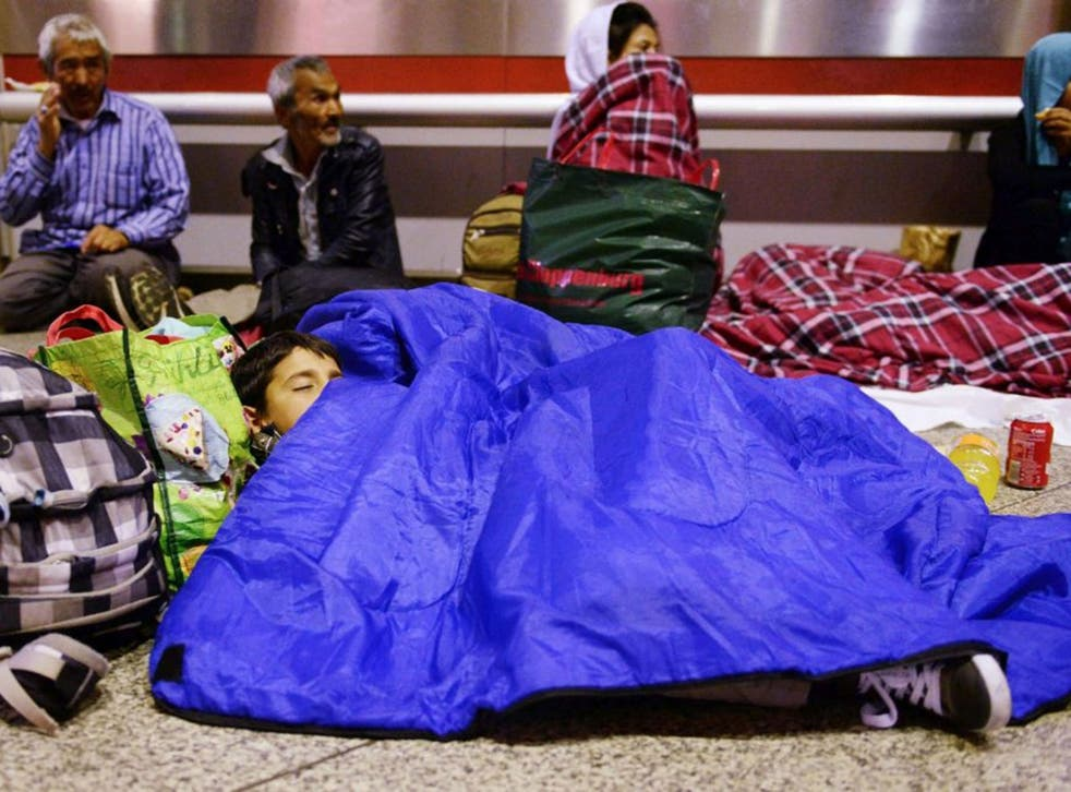 A refugee child from Afghanistan sleeps in the main hall of the train station in Munich, Germany, late 10 September 2015, as in the background other refugees are sitting. Germany expects 800,000 asylum seekers this year, four times more than last year and more than any other country in the European Union, which is split on how to deal with the biggest refugee crisis since World War II.